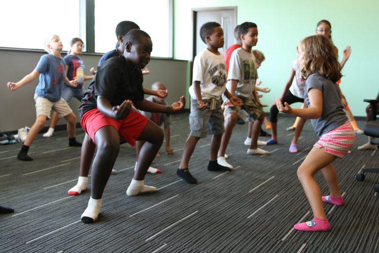 Group of kids doing a yoga pose.