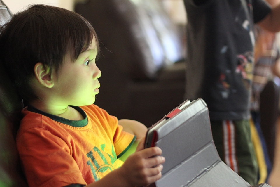 A kid holding a tablet while using a workout app