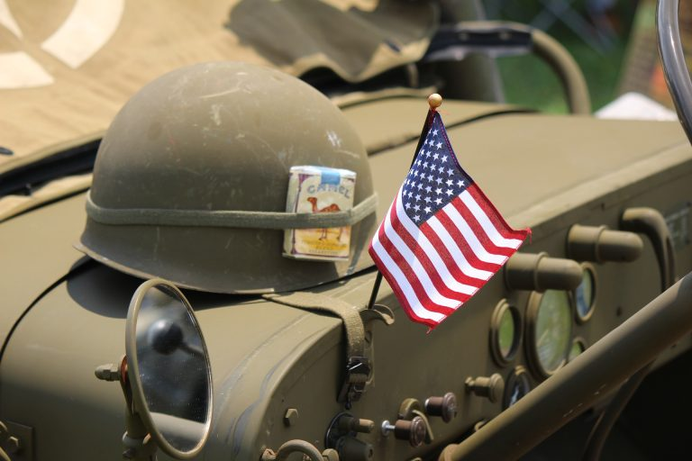 Army tank with helmet and American flag on top - honor our veterans on memorial day