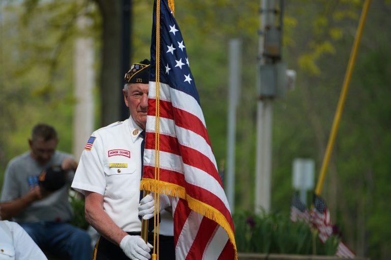 Elderly veteran holding American flag in memorial day parade