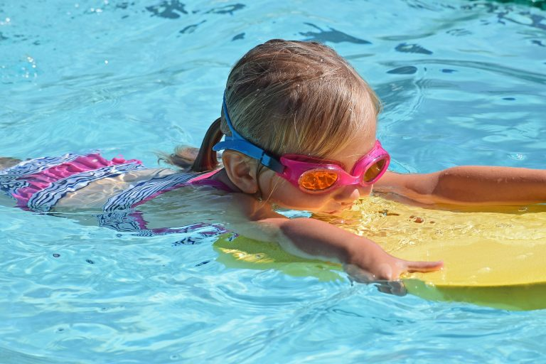 Little girl swimming in the pool with a flutter board and goggles.