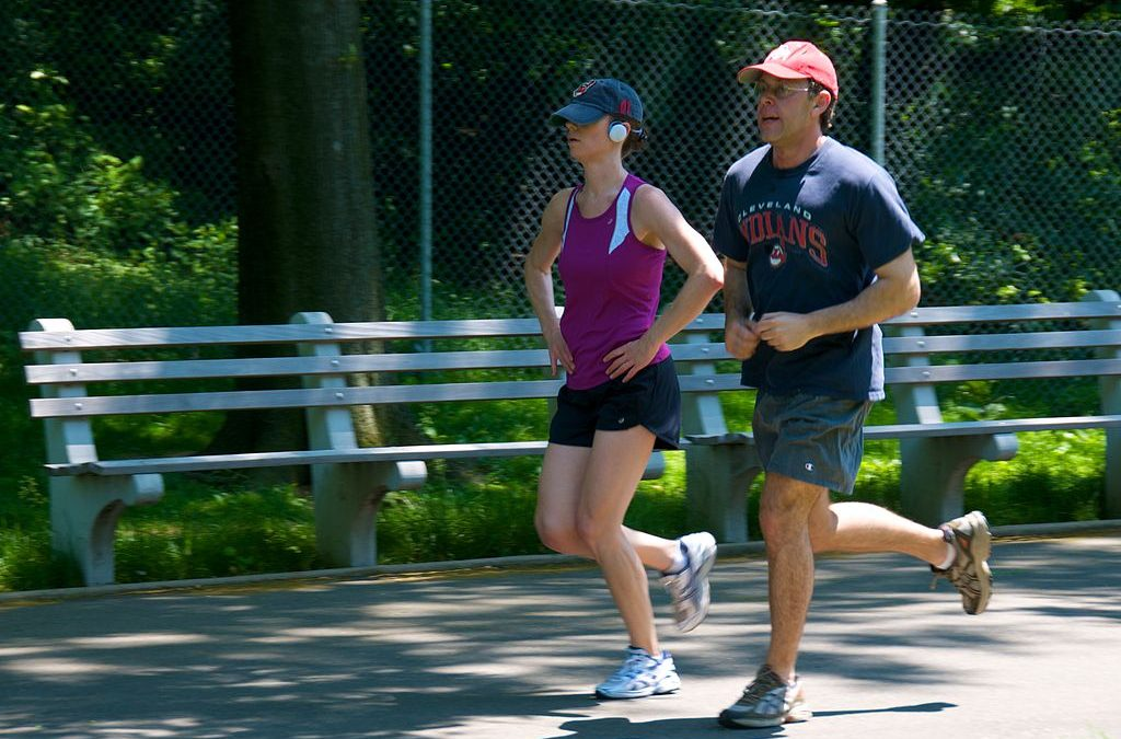 A man and woman are jogging in the park as part of their Fitquest fitness quest