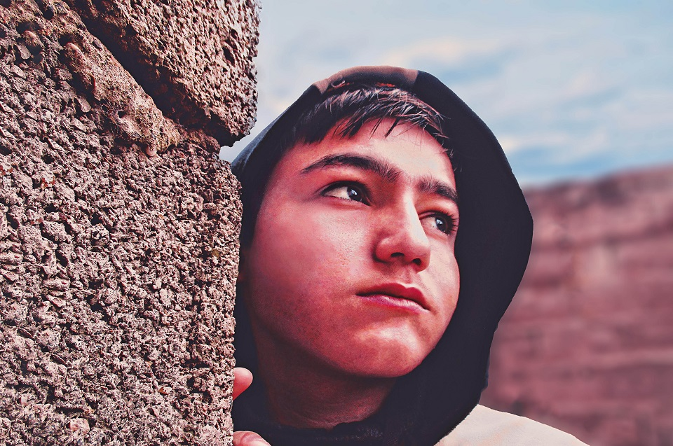 Hispanic teenage boy with a hoodie on, standing by rocks. Is he dealing with teenage problems?