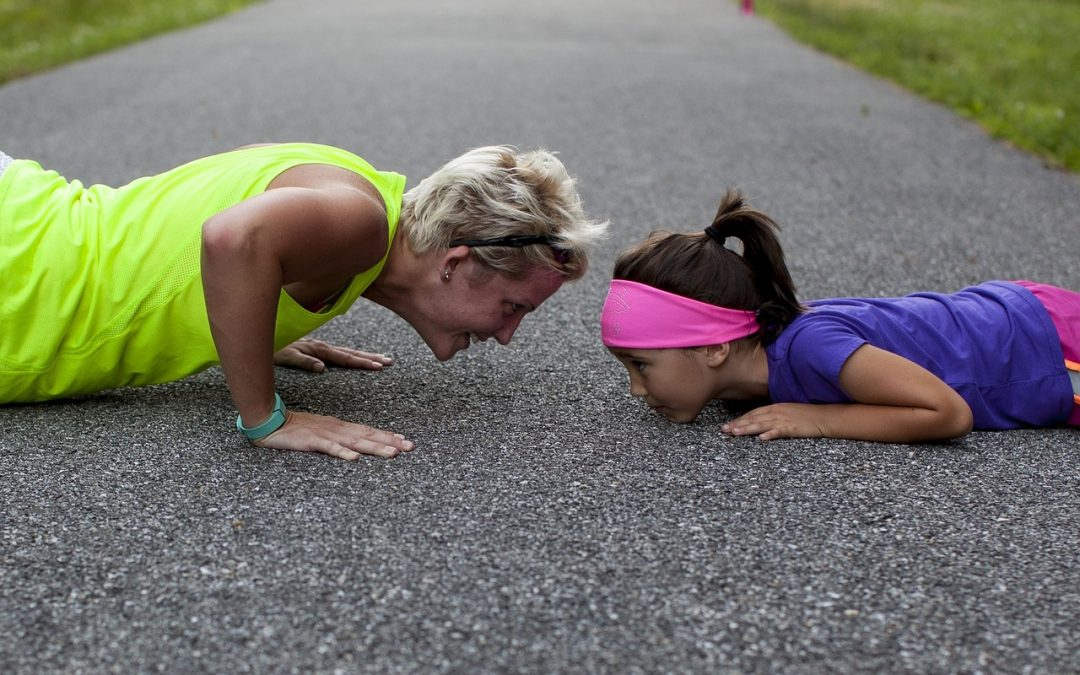 A mom and her young daughter are doing push-ups together as part of their Fitquest fitness quest.