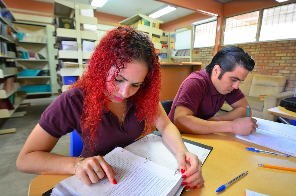 A teenage girl and a teenage boy in a library. School worries are another source of teenage problems