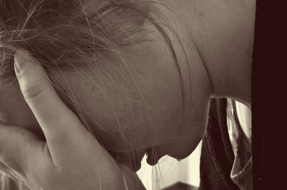 Teenage girl with her head in her hands. Depression is one component of teenage problems