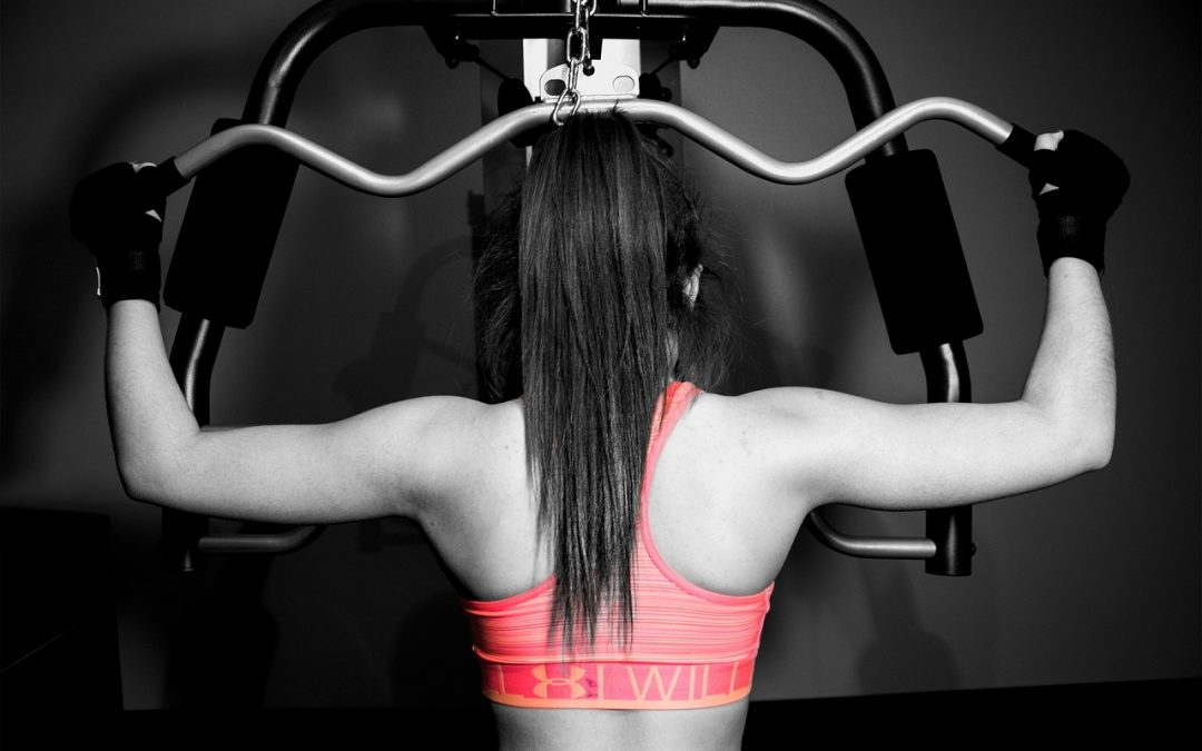 A physically fit woman is using gym equipment to build upper body strength as part of her Fitquest fitness routine.