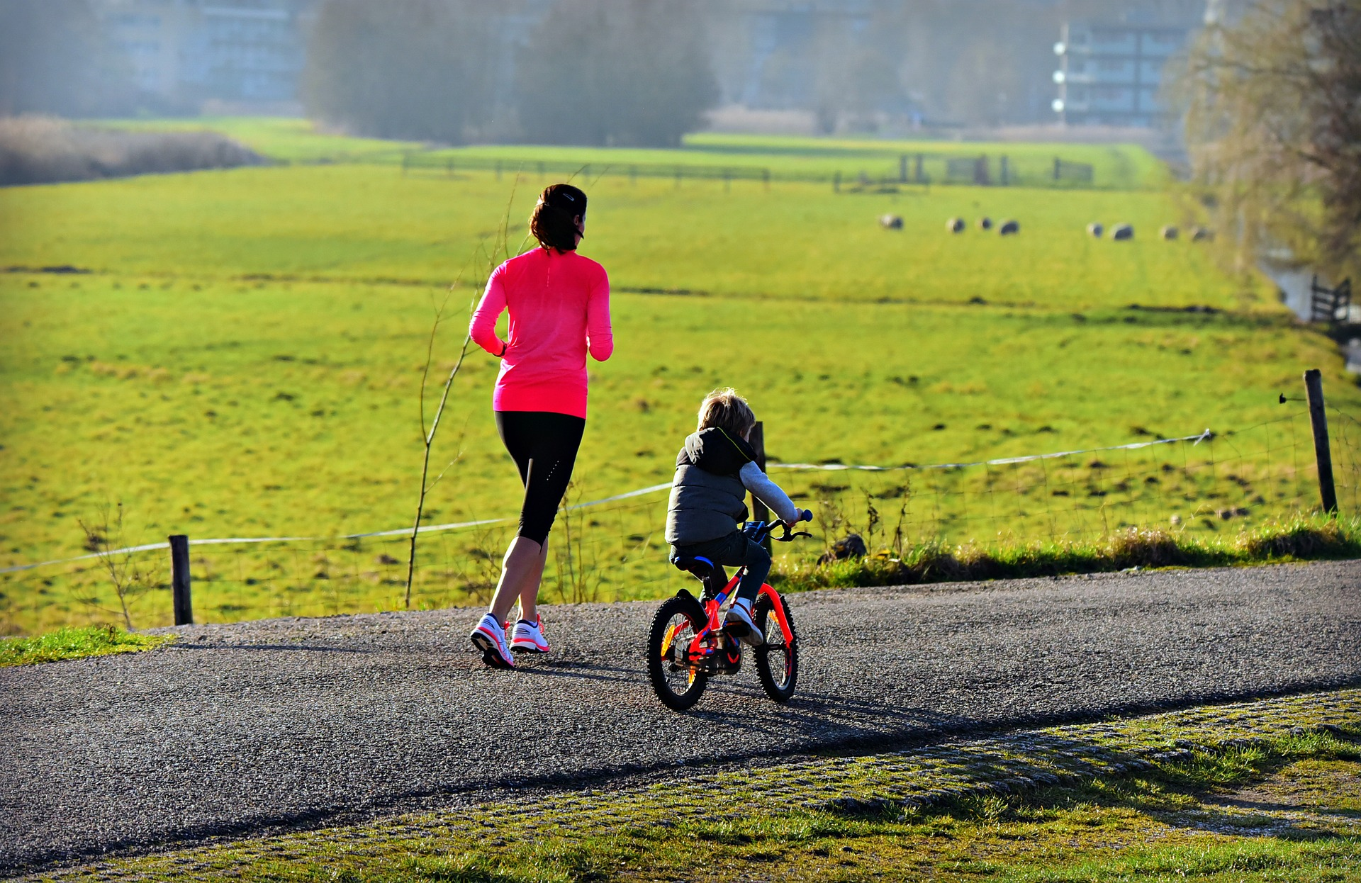 a mom jogging with her daughter while riding a bike
