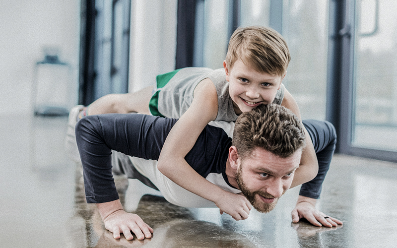 dad doing push ups with son on his back