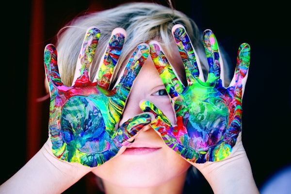 Adorable child with a colorful paint on her palms
