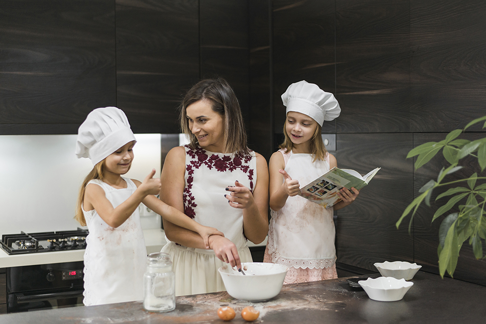 two kids cooking with mother and cookbook