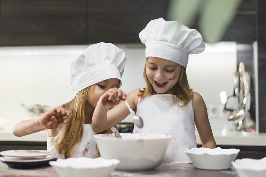 happy kids cooking at the kitchen