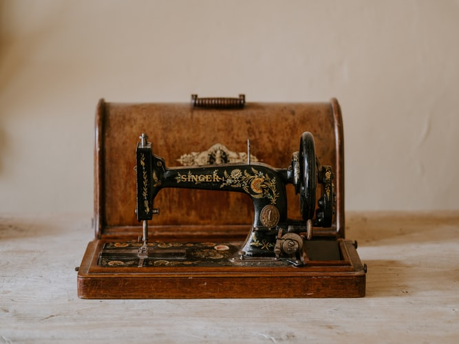black sewing machine with brown woden case
