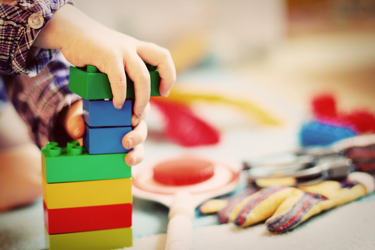 hand of a toddler playing colorful blocks